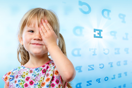 Photo for Close up portrait of little girl reading eye chart. Young kid testing one eye on block letter vision chart. - Royalty Free Image