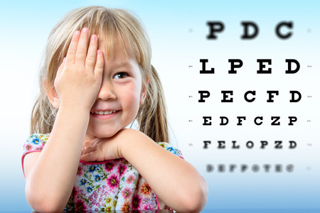 Photo pour Cute little girl reviewing eyesight.Girl closing one eye with hand reading block letters on vision chart with focus point. - image libre de droit