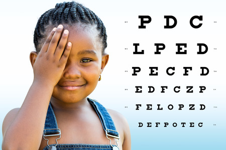 Foto de Close up portrait of Little african girl testing eyesight. Girl with braided hairstyle closing on eye with hand. Vision chart with block letters in background. - Imagen libre de derechos