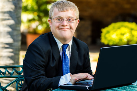 Foto de Close up portrait of young businessman with down syndrome doing accounting on laptop outdoors. - Imagen libre de derechos