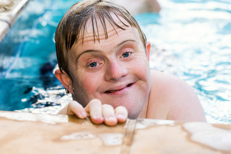 Photo for Close up face shot of handicapped boy in swimming pool. - Royalty Free Image