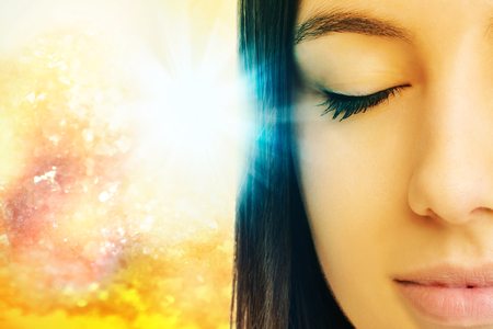 Photo pour Macro close up of young woman meditating with eyes closed.Conceptual spiritual background with light beam. - image libre de droit