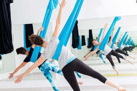 Foto de Close up of women exercising bodies at aerial yoga session in gym. - Imagen libre de derechos