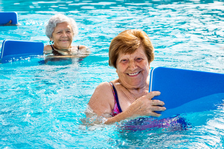 Foto de Close up portrait of two senior women doing aqua gym with kicking boards in outdoor swimming pool. - Imagen libre de derechos