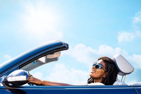 Photo pour Close up portrait of attractive elegant african woman driving convertible under sunny sky. - image libre de droit