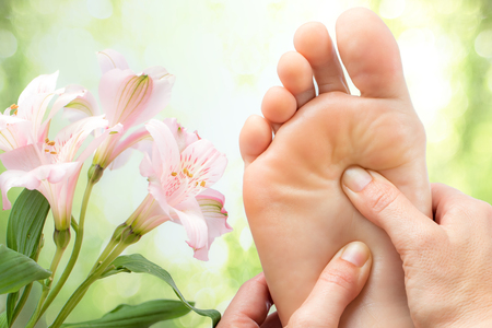 Photo pour Macro close up of foot massage next to colorful flowers and green background. - image libre de droit