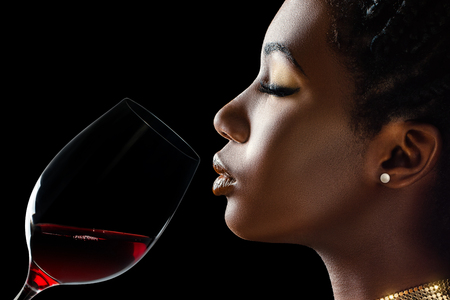 Foto de Macro close up low key portrait of sensual african woman smelling red wine.Side view of girl with red wine glass next to face against black background. - Imagen libre de derechos