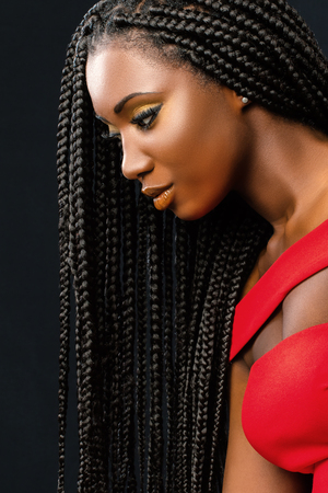 Photo pour Close up vertical beauty portrait of young african woman with long braided hair against dark background. - image libre de droit