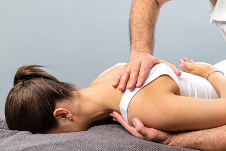Photo pour Close up detail of mail physiotherapist applying pressure on female shoulder blade.  - image libre de droit