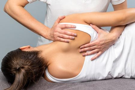 Photo pour Close up of detail of female physiotherapist doing shoulder blade treatment on patient. - image libre de droit