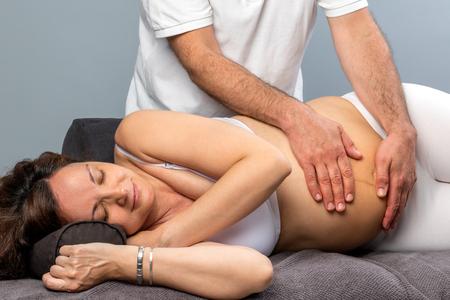 Photo pour Close up of male physiotherapist massaging tummy on pregnant woman. - image libre de droit