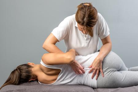 Photo pour Female physiotherapist doing manipulative spine treatment on young patient. - image libre de droit