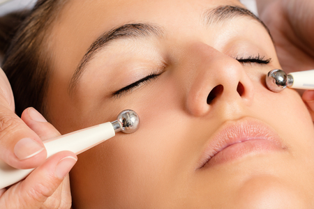 Photo for Close up portrait of woman having Galvanic facial treatment with low level current electrodes. - Royalty Free Image