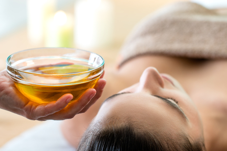 Photo for Macro close up of hand holding glass bowl with aromatic oil next to woman's head in spa. - Royalty Free Image