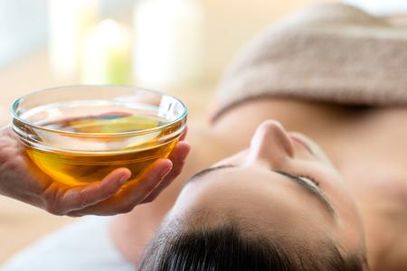 Foto de Macro close up of hand holding glass bowl with aromatic oil next to woman's head in spa. - Imagen libre de derechos