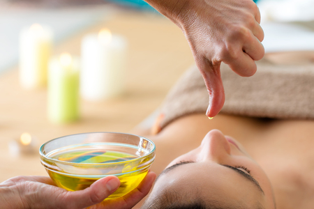 Photo pour Macro close up of hand with oil drop above woman's head in spa. Aromatic oil in glass bowl next to woman at Ayurvedic massage. - image libre de droit