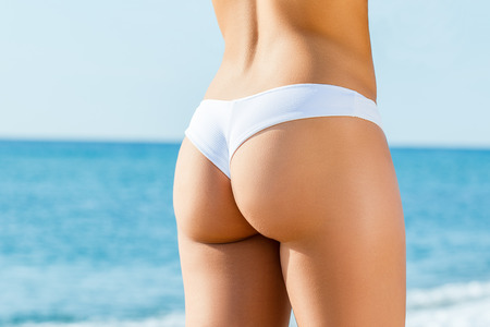 Foto de Close up detail of female buttock in white bikini outdoors. Rear view of slim woman with tanned skin tone. - Imagen libre de derechos