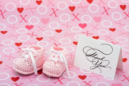 A white thank you card with baby booties on a pink love background, thank you note