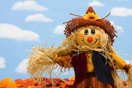 Photo for A scarecrow sitting on fall leaves on a sky background, scarecrow - Royalty Free Image