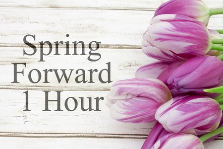 Foto de Some tulips with weathered wood and text Spring Forward 1 Hour - Imagen libre de derechos