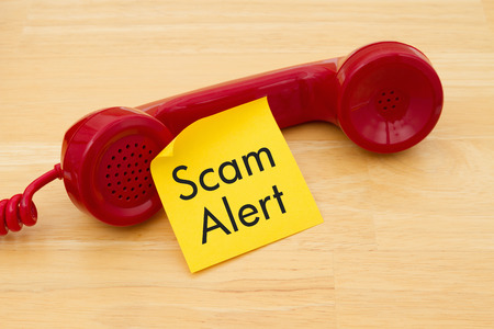 Photo pour A retro red phone with yellow sticky note on a desk with text Scam Alert - image libre de droit