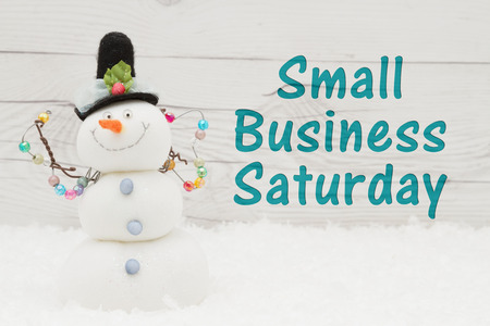 Photo pour Some snow and a snowman on weathered wood with text Small Business Saturday - image libre de droit