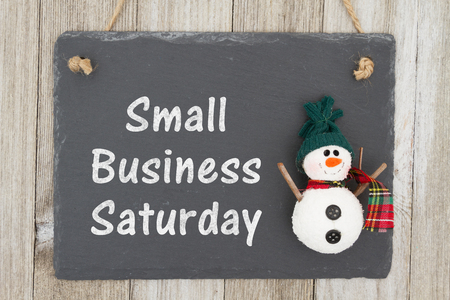 Photo pour A retro chalkboard with a snowman hanging on weathered wood background with text Small Business Saturday - image libre de droit