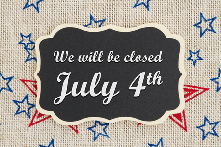 Foto de We will be closed July 4th text on a chalkboard with patriotic USA red and blue stars on burlap - Imagen libre de derechos