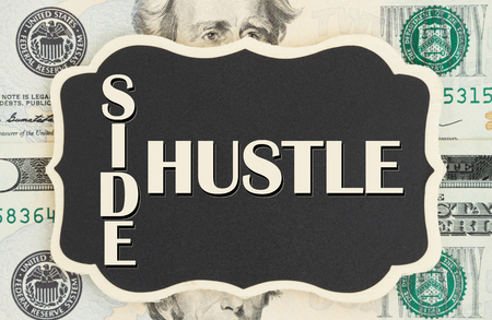 Photo pour Making money with your side hustle, Side Hustle text on chalkboard on USA twenty dollar bills - image libre de droit