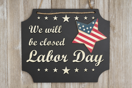 Foto de We will be closed Labor Day text on a chalkboard with patriotic USA red and blue star on weathered wood - Imagen libre de derechos