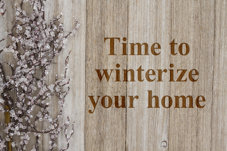 Foto de Time to winterize your home text with a iced tree branch on weathered wood - Imagen libre de derechos