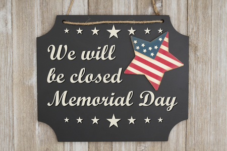 Foto de We will be closed Memorial Day text on a chalkboard with patriotic USA red and blue star on weathered wood - Imagen libre de derechos
