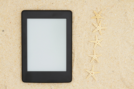 Foto de A blank e-reader on the beach for your summer reading that you can use as a mock up for your message - Imagen libre de derechos