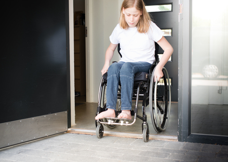 Photo for Young person in a wheelchair moving over a low doorstep - Royalty Free Image