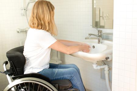 Photo pour Young person in a wheelchair washing hands - image libre de droit