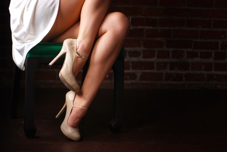Woman sitting in chair with legs and stilettoes