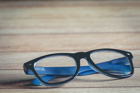 close up glasses on wooden background, vintage tone