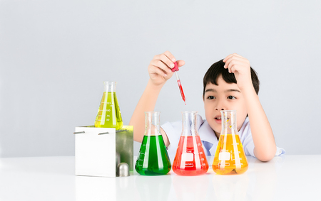 Foto de Asian little boy having fun in the liquid droplets red into the test beaker on white table and background,  Easy Science experiment for children, Education concept - Imagen libre de derechos