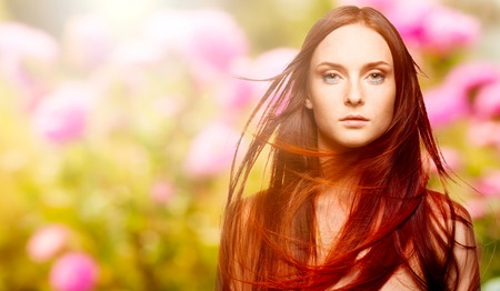 beautiful young woman with windy red hair over autumn background