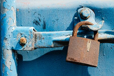 Photo for Old rusty lock on a blue background hanging on a sea shipping container. - Royalty Free Image
