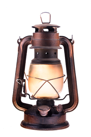 Photo pour Gas lantern with burning light, isolated on a white background. An antique vintage lamp. Hipster accessory. Camping light. Interior decoration. Oil lamp. Kerosene lantern. Rusty, covered with patina. Metal case, smoked frosted glass.  - image libre de droit