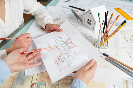Foto de Interior designers working on color hand drawings of a kitchen interior at work place. Photo of young designers work concept - Imagen libre de derechos