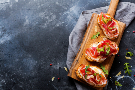 Photo pour Open sandwiches with jamon, arugula and hard cheese on a wooden stand on a concrete old dark background. Rustik style. Top view. - image libre de droit