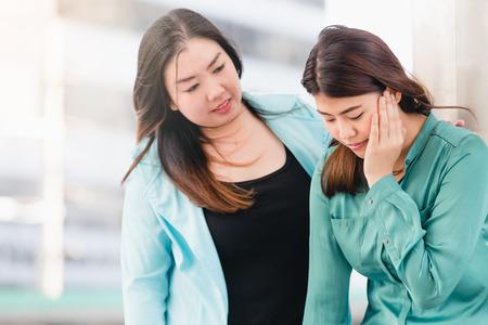 Foto de Asian woman comforting her mourning friend outdoor in city - Imagen libre de derechos