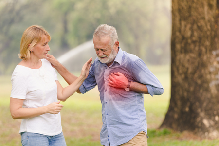 Foto de Senior men cardiac arrest heart attack in park.Severe heartache - Imagen libre de derechos