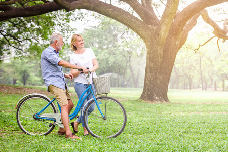 Photo pour Senior couple walking their bike along happily talking happily. - image libre de droit