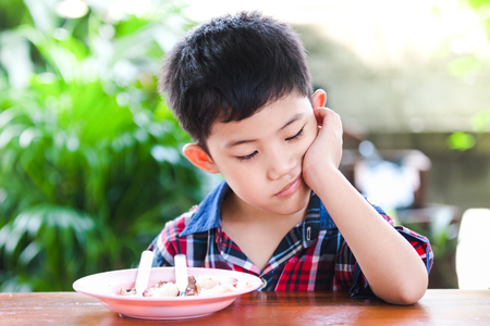 Photo pour Asian little boy boring eating with rice food on the wooden table - image libre de droit