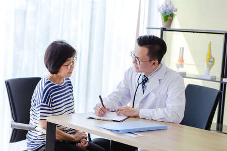 Foto per Old Patient Woman Talking with Medical Doctor Man in office - Immagine Royalty Free