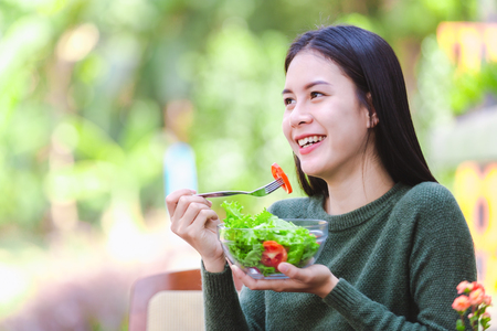 Foto de Asian beautiful young girl eating salad vegetable outdoor , Concept healthy body - Imagen libre de derechos