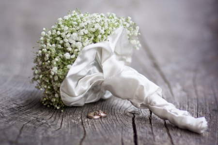 Wedding  bouquet and rings on a dark wooden background.